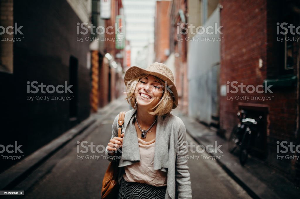 Urban life portrait of smiling woman in the middle of a narrow street. stock photo
