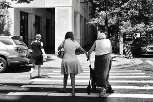 Urban Life, Senior female pedestrian with walker being helped to cross street, Lower Manhattan, New York City, USA stock photo