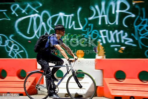 New York City, USA - June 21, 2014: A male bicyclist passing by a construction site barrier full of graffiti in Williamsburg, Brooklyn.