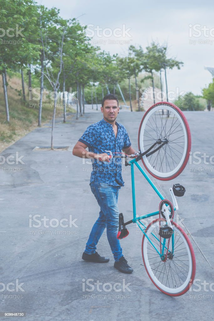 Urban man holding his bike casual wearing stock photo