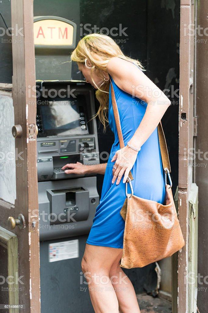 Urban Mature Blond Woman using an ATM photo libre de droits