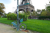 Paris, France. October 04. 2020. Electric bike rental used by tourists. Historic monument in the background. Eiffel Tower, visited by millions of people.