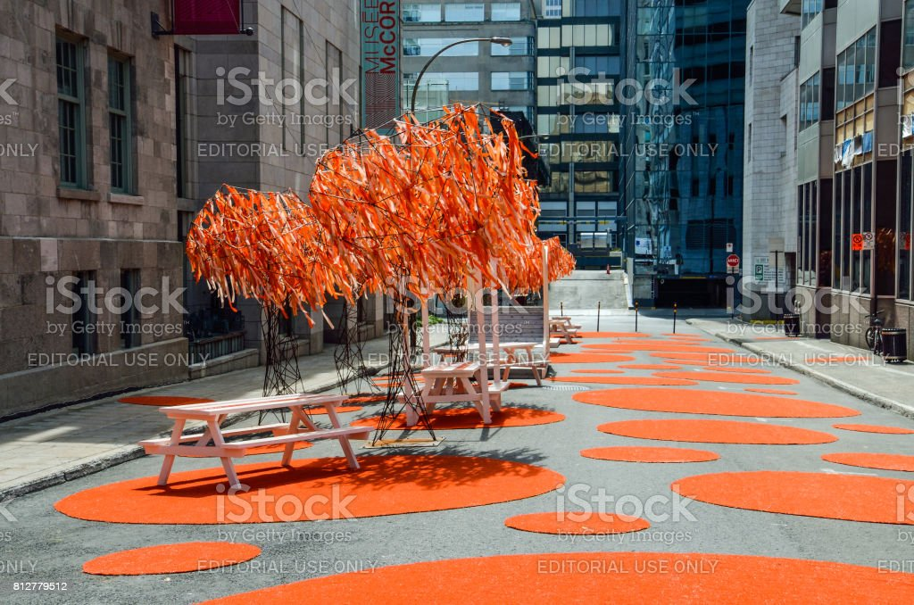 Urban modern art installation in downtown with green trees and circles on street stock photo