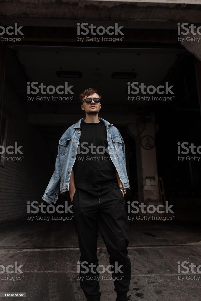 Urbano Moderno Y Elegante Joven Hipster Hombre En Negro Pantalones De Moda En Una Chaqueta De Jeans Azul Vintage En Gafas De Sol Negros Sale Del Edificio Oscuro Un Tipo De Moda