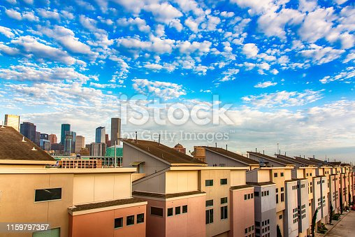A neighborhood of row houses near downtown Houston, Texas with the skyline of the city beyond.