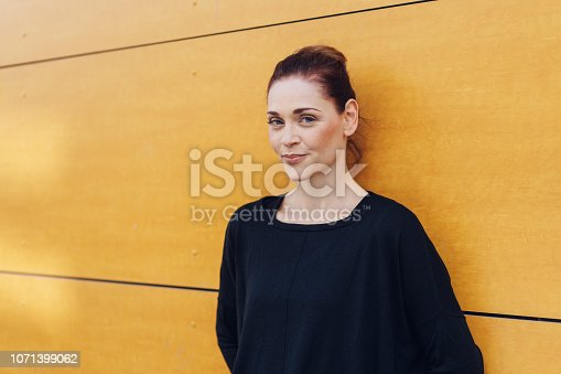A portrait of a pretty caucasian woman smiling at camera while leaning against a yellow wall in an urban setting.