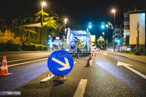 Central European infrastructure maintenance crew repainting urban street surface markings at night.