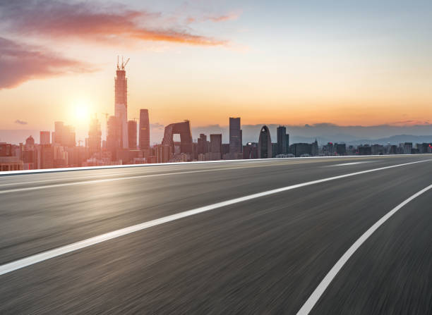 stedelijke weg in zonlicht - stadsweg stockfoto's en -beelden
