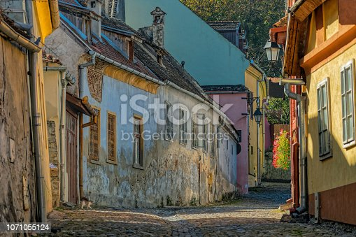 Urban road with cubblestones and multi colored medieval houses in Sighisoara, Transyvania, Romania