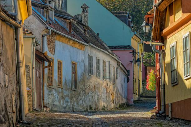 Städtische Straße mit Cubblestones und Multi farbige mittelalterliche Häusern in Sighisoara, Transyvania, Rumänien – Foto