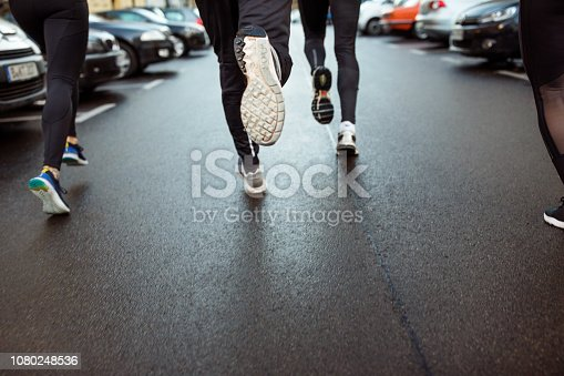 Low angle rear view of young people running on the city street. Focus on feet of urban runners, jogging in morning.