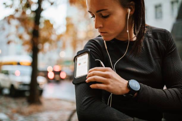 urban runner einrichten ihres smartphones vor dem training - joggerin stock-fotos und bilder