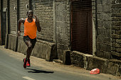 urban runner workout . Young attractive and athletic black afro American man running outdoors on asphalt road training hard jogging in sport sacrifice commitment and healthy lifestyle concept
