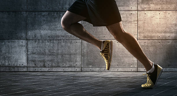 Urban running Close up of urban runner's legs run on the street with copy space endurance stock pictures, royalty-free photos & images