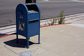 One od set. Mailbox and weeds on sidewalk.