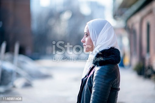 A Muslim woman is outdoors on a sunny day. She is wearing casual clothing and a head scarf. She is standing near a road and staring out onto the street.