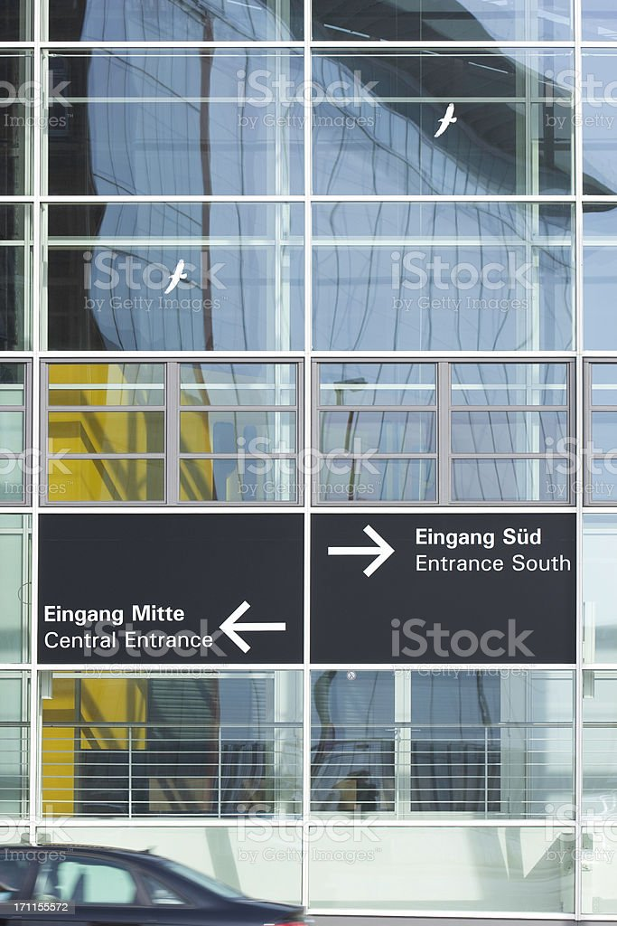 front of a huge glass facade. two white stickers with silhouttes of...