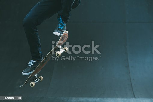 Urban skater in action. Ollie trick. Skate park ramp. City area. Man on skateboard jumping. Copy space for text.
