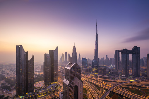 Urban skyline and cityscape at sunrise in Dubai UAE.