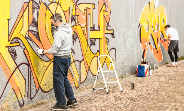 Artistas urbanos calle pintura colorido graffiti en pared genérica - concepto de arte moderno con chicos realizando murales vivos de color aerosol spray filtro neutro cálido - foco izquierdo persona- - foto de stock