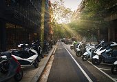 Barcelona, Spain - 06 15, 2019: This image shows a small city urban street lined with people's scooters and bikes with rays of sun shining through the alley.