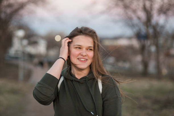 urban style and fashion concept. outdoor portrait of beautiful stylish young european female model with long brown hair wearing trendy hoodie and white sneackers watches, posing in evening autumn or spring park - spring fashion stock pictures, royalty-free photos & images