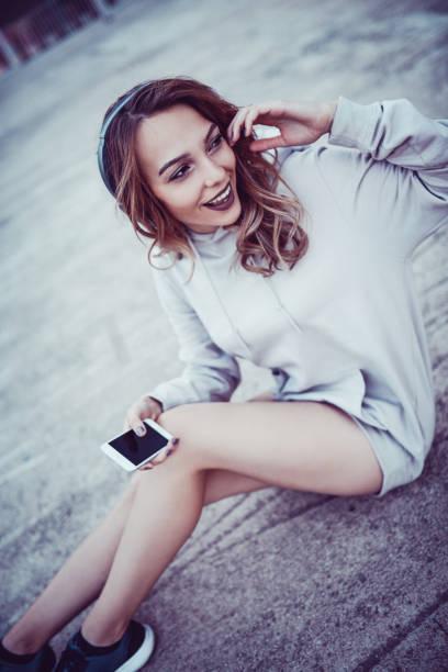 urban style weiblich genießen sie musik über kopfhörer und sitzen auf straße - hipster unterwäsche stock-fotos und bilder
