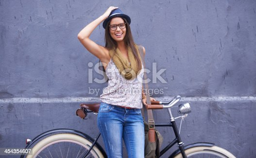 A gorgeous young woman standing with her vintage bicycle