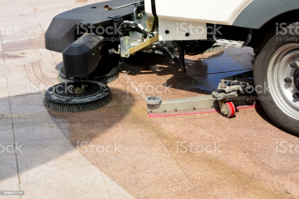 urban sweeper cleans road from dirt with a round brush stock photo