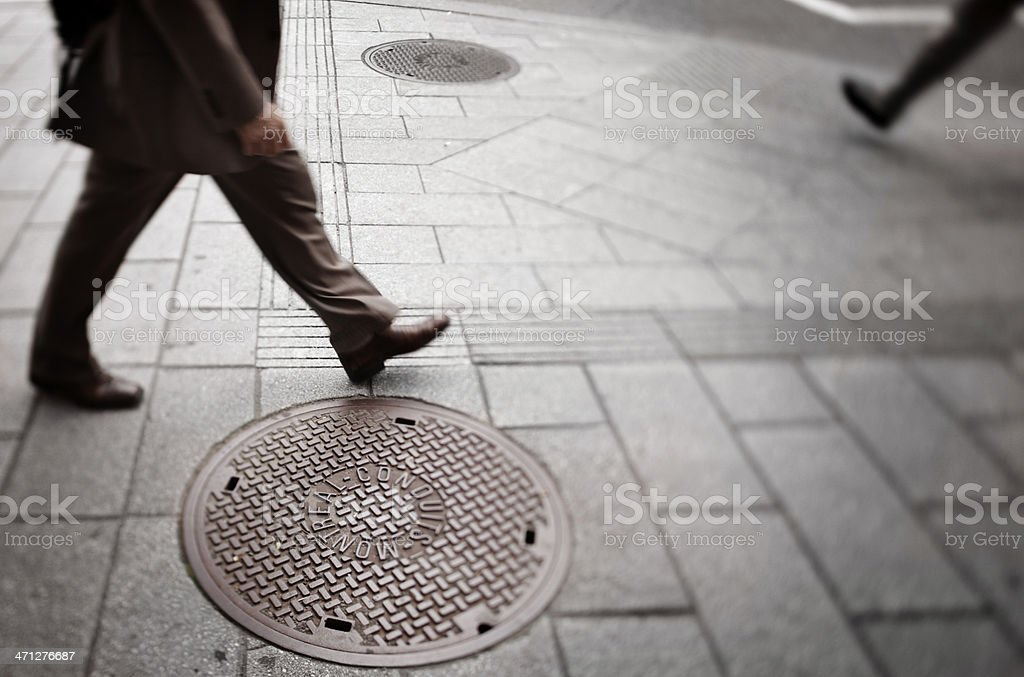 Urban Travel - Walking past manhole cover stock photo