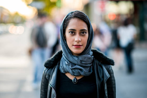 Urban Woman A Muslim woman is outdoors on a sunny day. She is wearing casual clothing and a head scarf. She is standing near a road and smiling at the camera. immigrant stock pictures, royalty-free photos & images