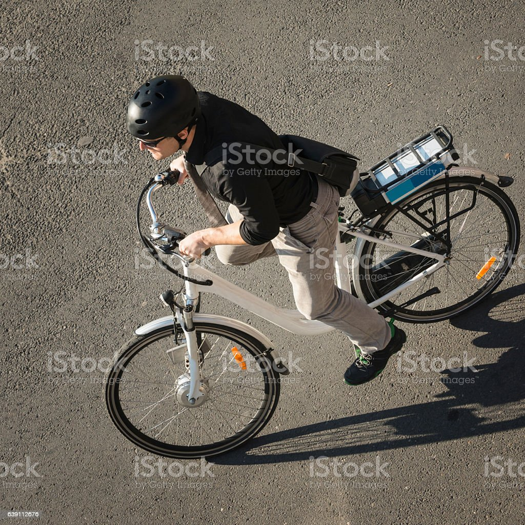 Urban young man riding electric bicycle stock photo