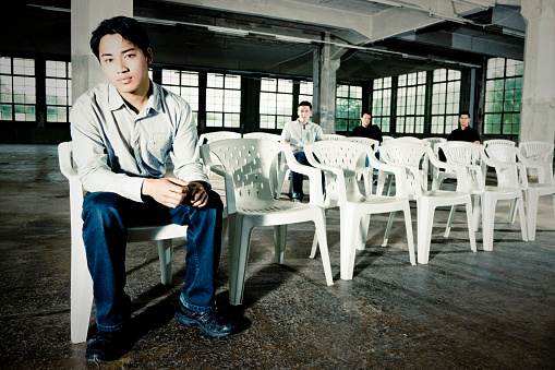 Young men sitting in white chairs in empty abandoned warehouse. Urban Lifestyle Group Portrait.