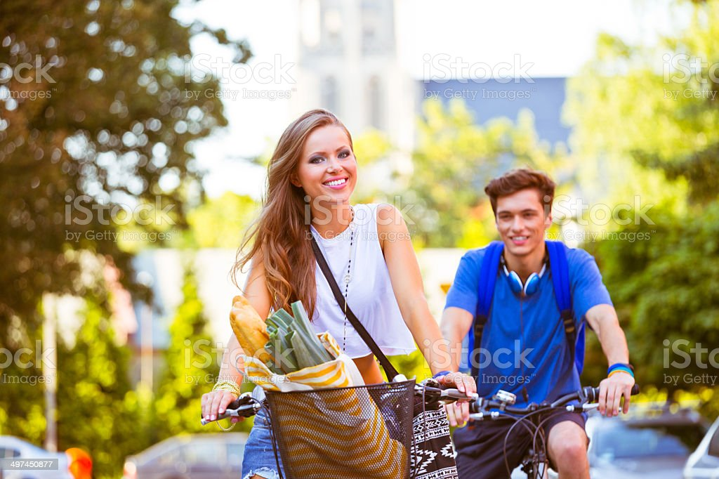 Urban young people cycling Young woman and man cycling in the city, smiling at camera. 20-24 Years Stock Photo