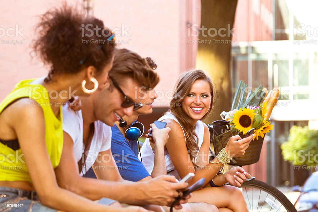 Urban young people Four young people using smart phones outdoors. 20-24 Years Stock Photo