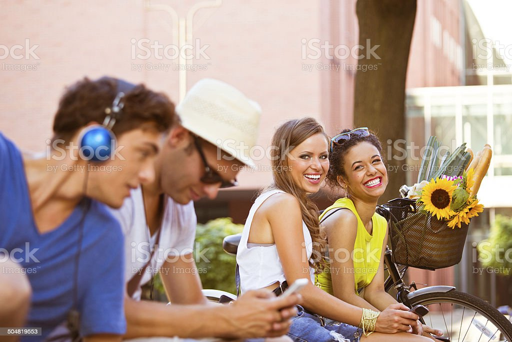Urban young people Four young urban people sitting outdoors and using their smart phones. Focus on two smiling girls sitting in the background. 20-24 Years Stock Photo