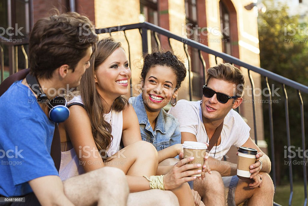 Urban young people Four young urban people sitting outdoors, holding take away coffee and enjoying common time. 20-24 Years Stock Photo