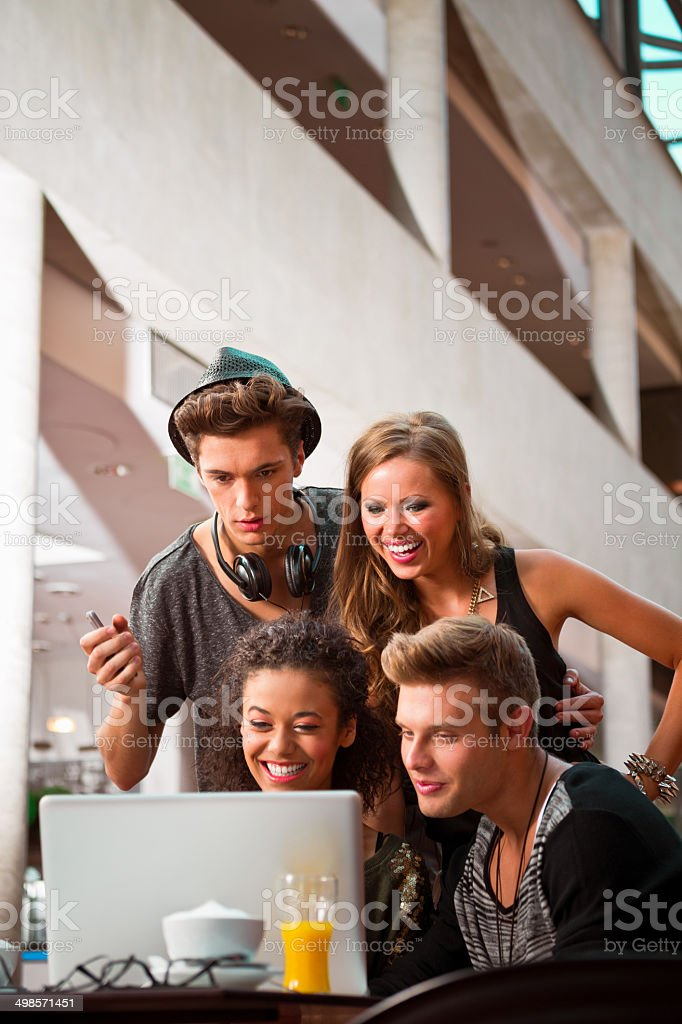 Urban young people using laptop Cheerful young urban people using laptop together. 20-24 Years Stock Photo