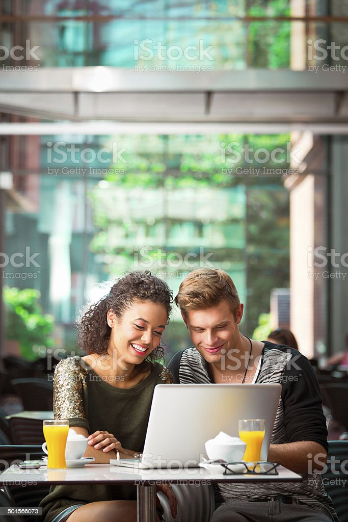 Urban young people using laptop Cheerful young couple sitting in cafe, using laptop together. 20-24 Years Stock Photo