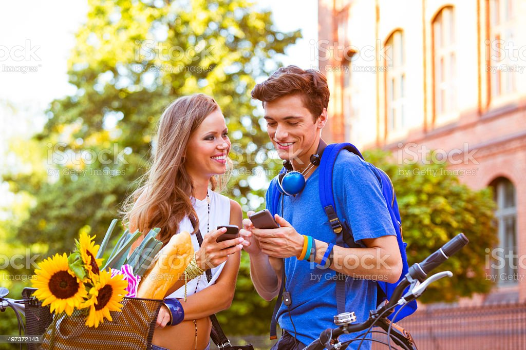 Urban young people using smart phones Outdoor portrait of young couple using their smart phones. 20-24 Years Stock Photo