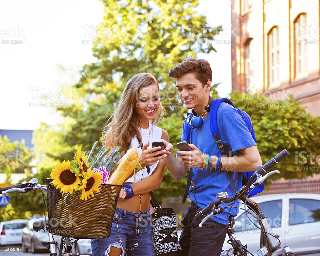 Urban young people using smart phones Outdoor portrait of urban young couple standing on the street with blicycles and using their smart phones. 20-24 Years Stock Photo