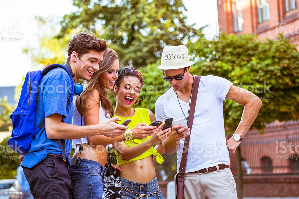 Urban young peoplewith smart phones Four happy young people using smart phones outdoors. 20-24 Years Stock Photo