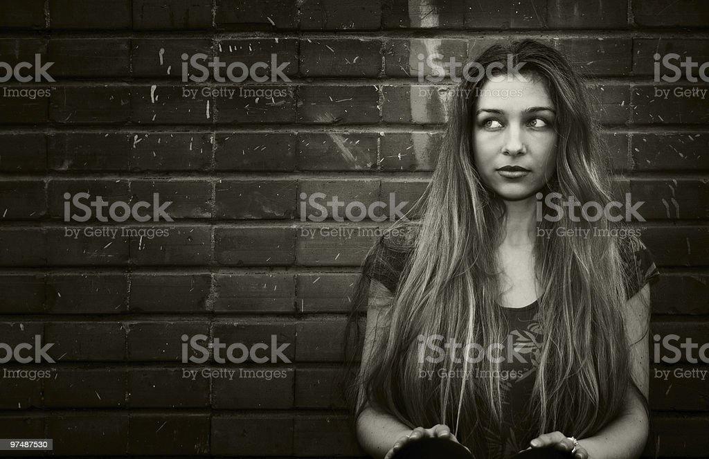 Urban young woman sitting near brick wall royalty-free stock photo