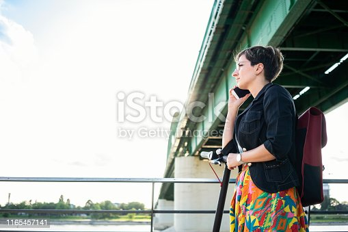 874772840istockphoto Urban young woman using electric scooter 1165457141