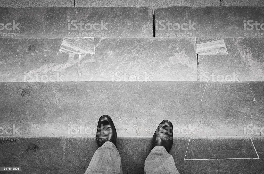 Urbanite man in black shoes on stone stairs stock photo