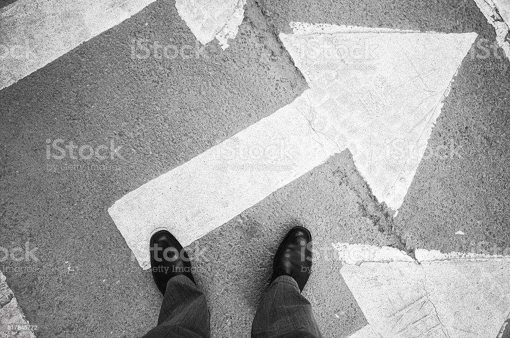 Urbanite man in shining shoes stans on arrow stock photo