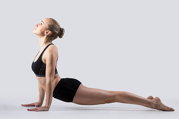 Urdhva mukha shvanasana pose Sporty beautiful young woman practicing yoga, doing urdhva mukha svanasana, upward facing dog pose (sun salutation asana), working out wearing black sportswear, studio, full length, side view upward facing dog position stock pictures, royalty-free photos & images