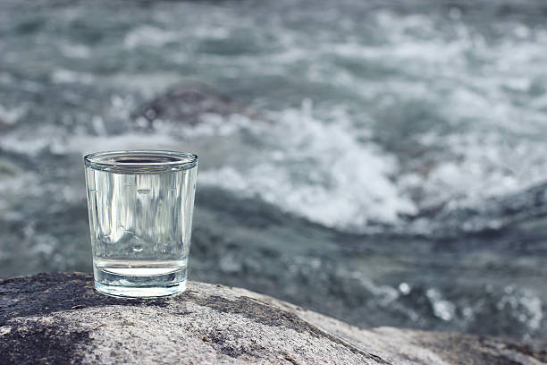 ure clean  drinking water  into a glass and mountain river stock photo