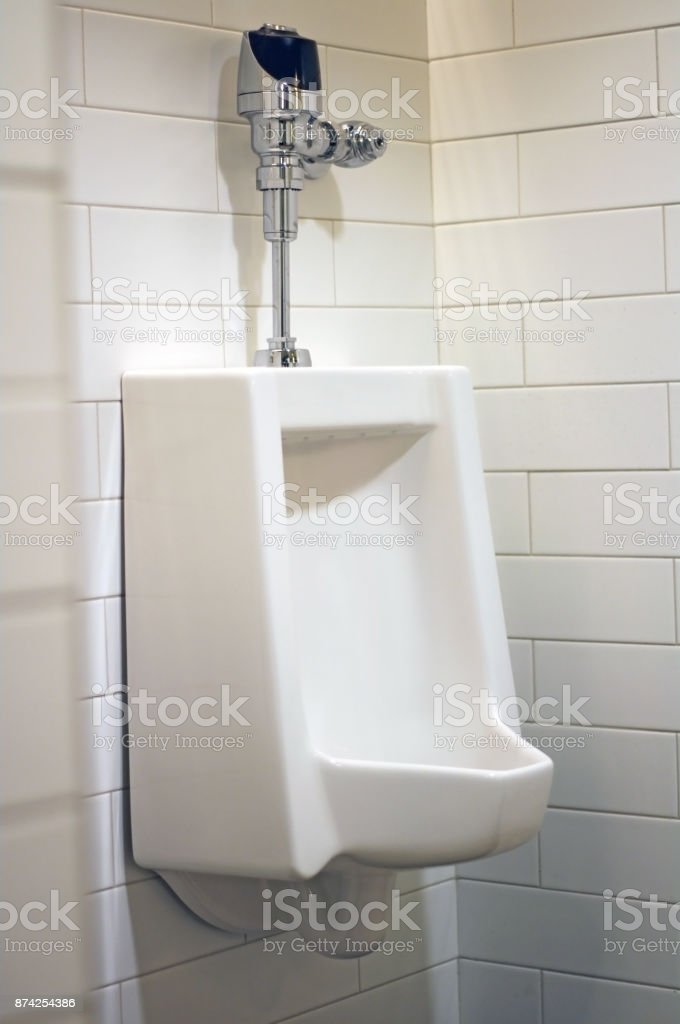 Urinal in mensroom with white tile stock photo