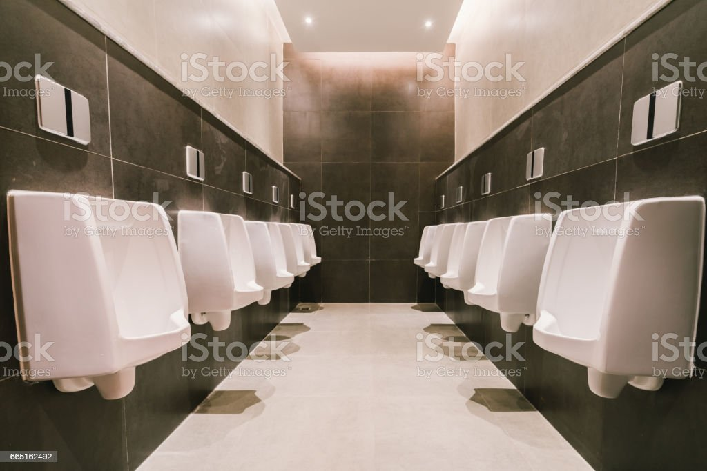 Urinals in men's public modern toilet, restroom sanitary or wc architecture design concept stock photo